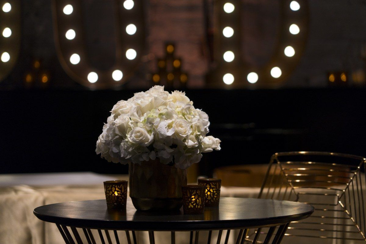 gold vase stand of gold vase with white flowers at black and gold event great gatsby with gold vase with white flowers at black and gold event