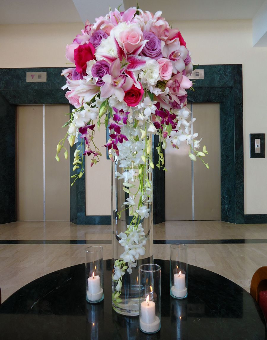 Hot Pink Vase Of Tall Centerpiece 31 Height Vase with A White Dendrobium Large with Tall Centerpiece 31 Height Vase with A White Dendrobium Large Strand Submerged Lilac Pink Fuchsia Roses Stargazer Lily and Fuchsia White Hanging