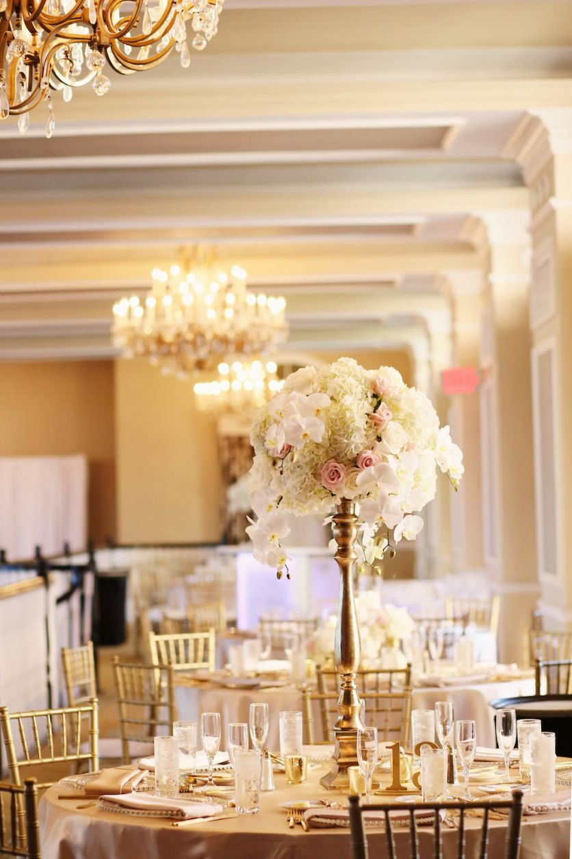 rose gold vase centerpiece of timeless elegant blush pink gold st pete beach wedding mmtb with tall wedding reception centerpiece with white hydrangeas and orchids blush roses in tall gold vase tampa bay wedding venue the don cesar st petersburg