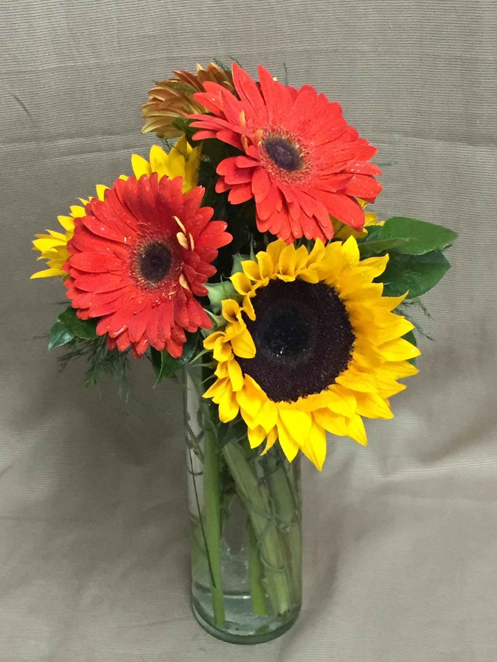 tall gold cylinder vases of brilliant birthday yellow sunflowers orange gerbera daisies salal for brilliant birthday yellow sunflowers orange gerbera daisies salal and tree fern in a tall cylinder vase