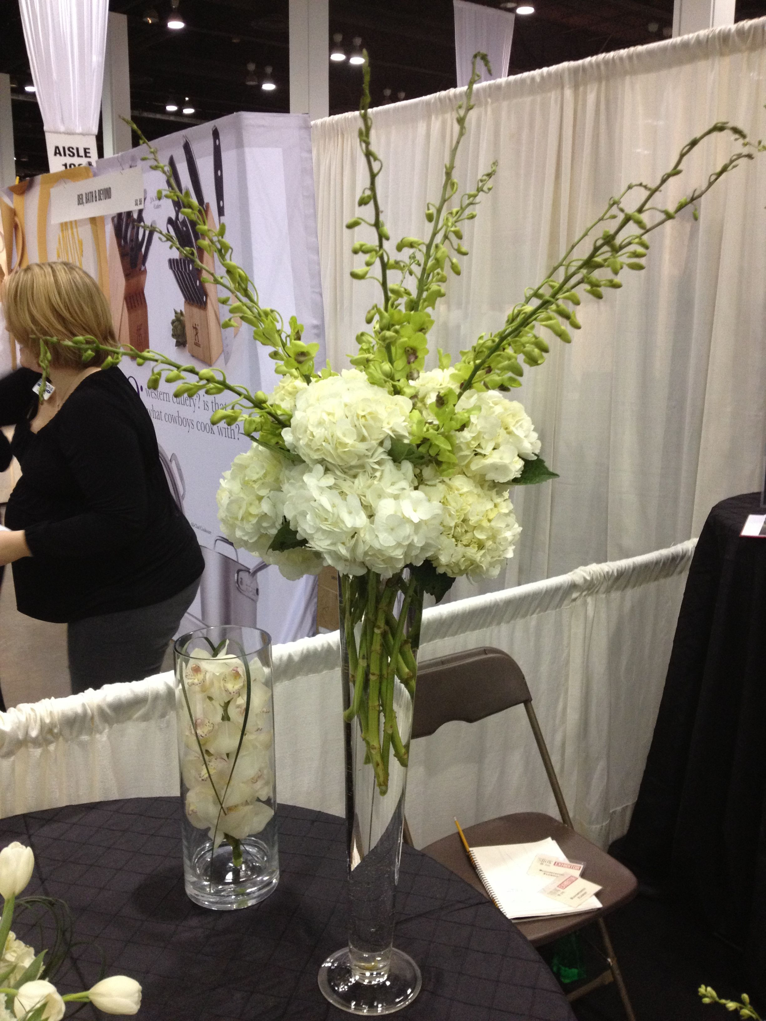 tall pewter vase of white hydrangea and green dendrobium orchids mounded on top of a within white hydrangea and green dendrobium orchids mounded on top of a tall pilsner vase