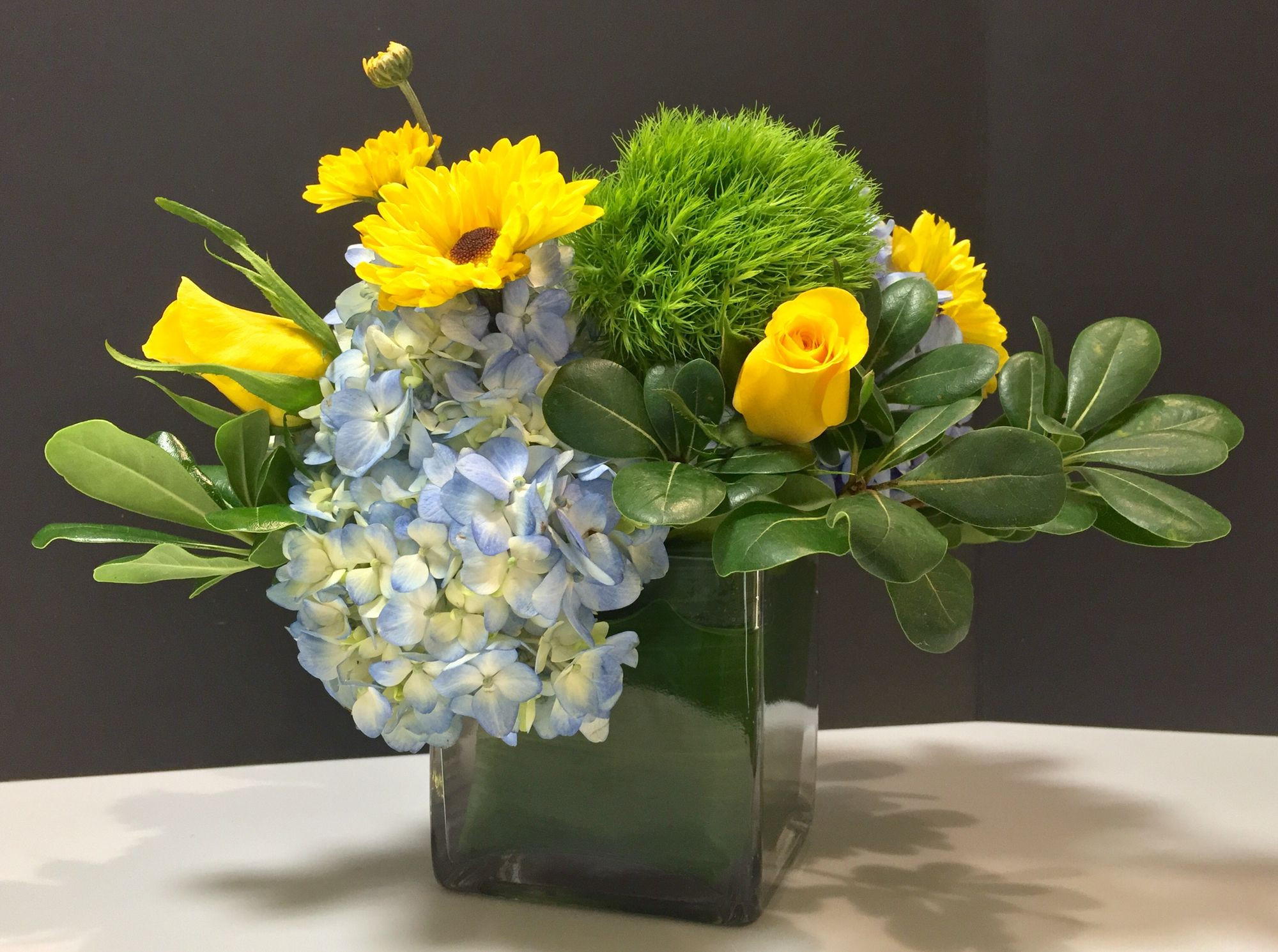 yellow rose vase of yellow roses light blue hydrangea green trick and pitasporum on in yellow roses light blue hydrangea green trick and pitasporum on cube vase wrapped in aspadistra leaf original design and arrangement by